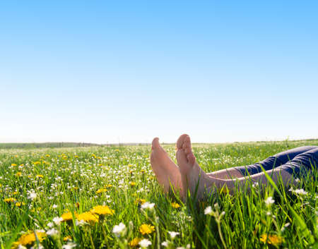 bare feet on spring grass and flowers Stock Photo