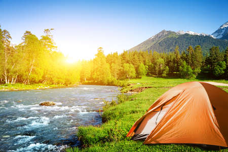 camp: tourist tent camping in mountains Stock Photo