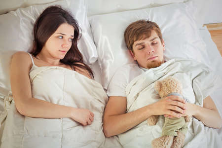childish: man with childish behavior sleeping in bed Stock Photo