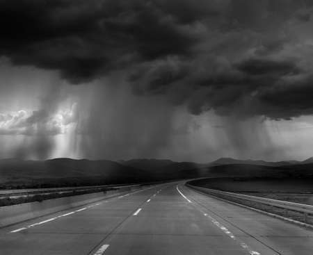 dark skies: Dark stormy clouds on road
