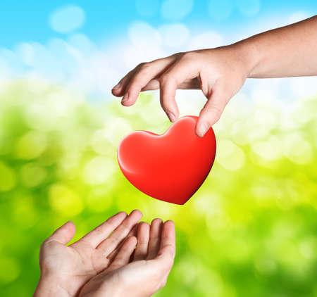Mains avec coeur rouge donnant le concept Banque d'images - 67444674