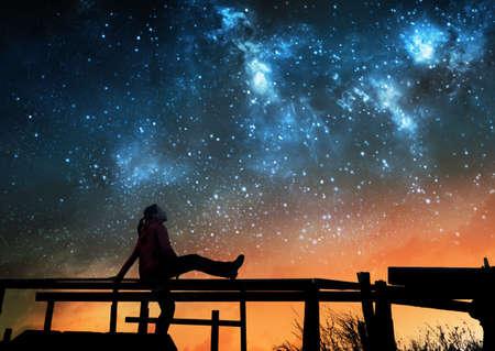夜空の星を見る少女
