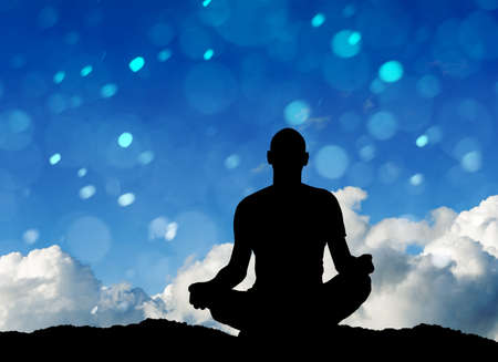 silhouette of man practicing yoga outdoors photo