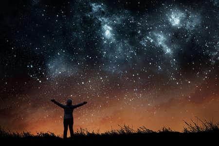 Chica mirando las estrellas en el cielo nocturno