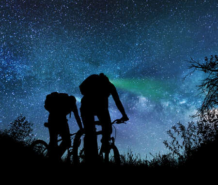 Couple ride bicycles at night under the milky way Stock fotó