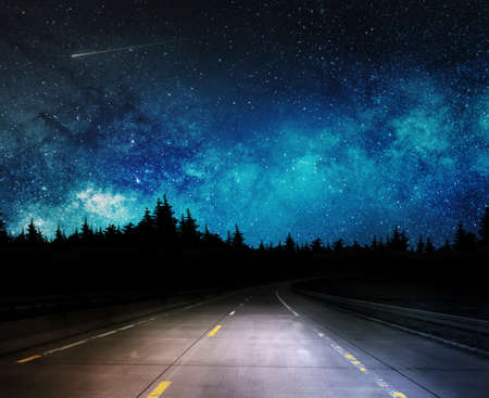 dark night road through forest and starry sky Banco de Imagens