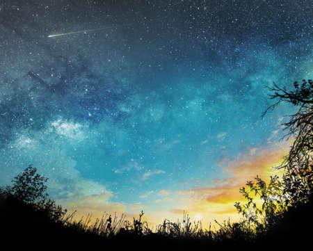 atardecer a fondo de cielo nocturno con estrellas, cometas y nubes