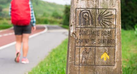 Way of St James , Camino de Santiago , sign shells marks for pilgrims to Compostela Cathedral , Spain ( Walk of Santiago ) Pilgrim with backpack walking along the pilgrimage Banco de Imagens