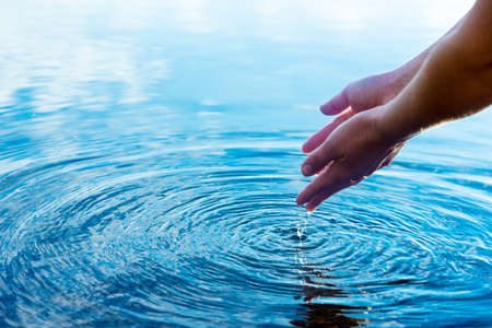hands in crystal clear water with drops, nature water concept