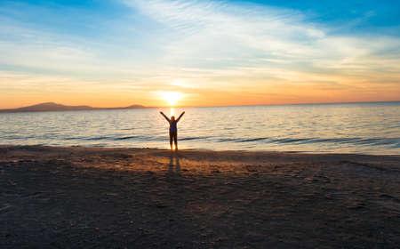 girl silhouette near sea at sunset