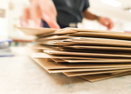 Close-up Brown Paper bag on desk with Blur Male office workers your hand Picking up something,business and Education concept,design for illustration. Stock Photo
