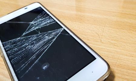 Smartphone mobile avec écran cassé verre sur fond de table en bois . Banque d'images - 93641651