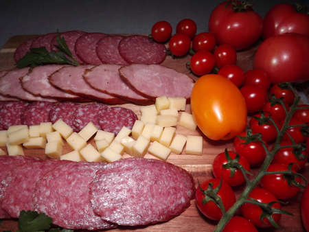slicing smoked sausage of four varieties with cheese and red and yellow tomatoes and cherry tomatoes. High quality photo