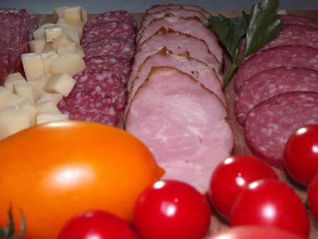 slicing smoked sausage of four varieties with cheese and red and yellow tomatoes and cherry tomatoes. High quality photo Standard-Bild