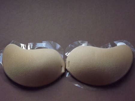 beige strapless bra close-up on different color backgrounds, size A. High quality photo Standard-Bild