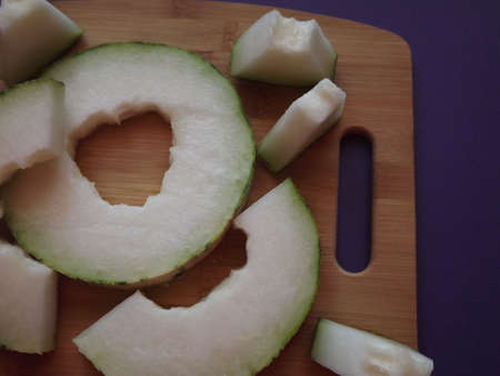 ripe melon cut into slices on a wooden board. High quality photo