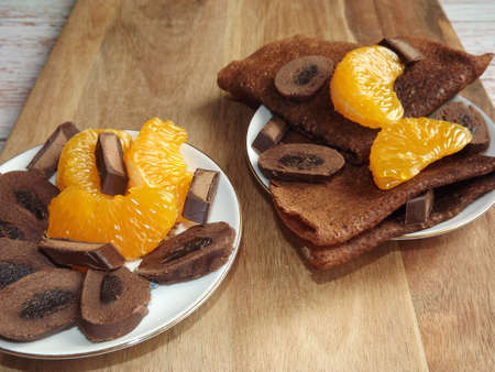 dessert with chocolate pancakes, chocolate with tangerine slices on a blue wooden background. High quality photo
