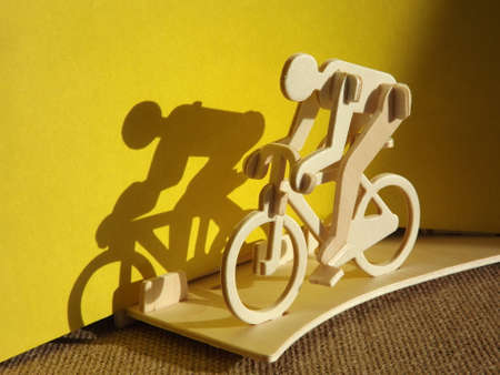cyclist on a bicycle made of wood on a yellow background. High quality photo Standard-Bild