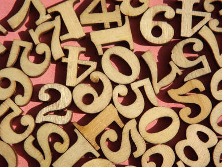 wooden numbers are randomly arranged on pink suede. High quality photo