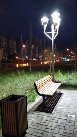 A park in the city in the evening with a view of a walking street, benches and a lantern. High quality photo