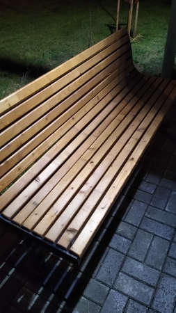 A wooden bench in a night park in the evening in the rain close-up. High quality photo