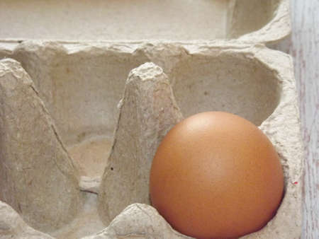 beige chicken eggs in an egg box on a light wooden background. High quality photo