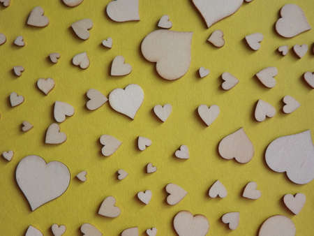 wooden hearts of different sizes on a yellow background. valentines day, a declaration of love. High quality photo