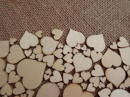 wooden hearts of different sizes on jute fabric as a Valentines day greeting card. High quality photo