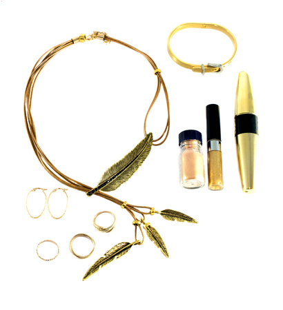 set of gold accessories and cosmetics on a white background Foto de archivo