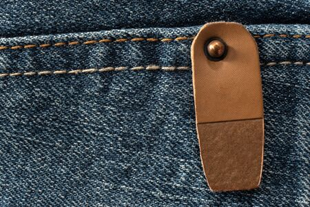 blank brown leather label pinned to seams of blue jeans fabric close-up, no people mock-up