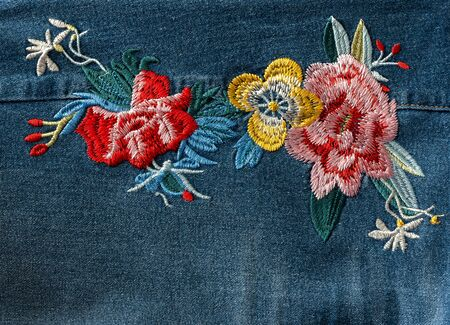 bright colored flowers embroidery on blue jeans denim