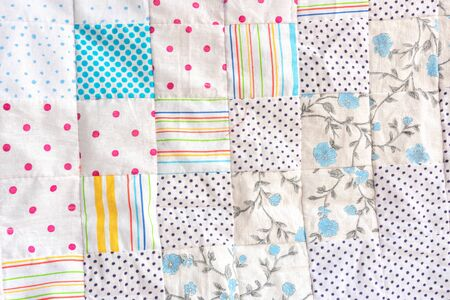 White patchwork quilt fragment. Colorful handmade ethnic blanket. Worn clothes reuse concept.
