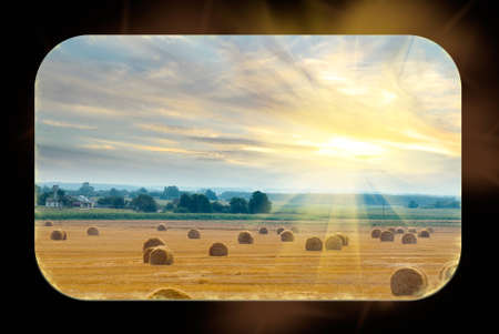 From the windows of the train can be seen field with bales of straw illuminated by the rays of the sun Stock Photo - 15173698