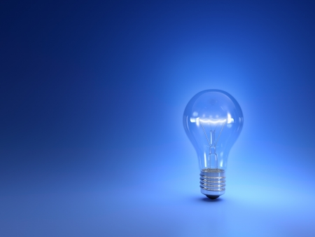 One simple glowing light bulb isolated on blue background photo