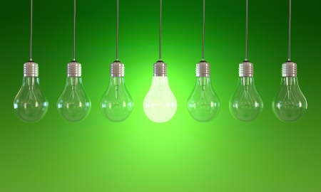 lighting equipment: Seven light bulbs with lit one on green background Stock Photo
