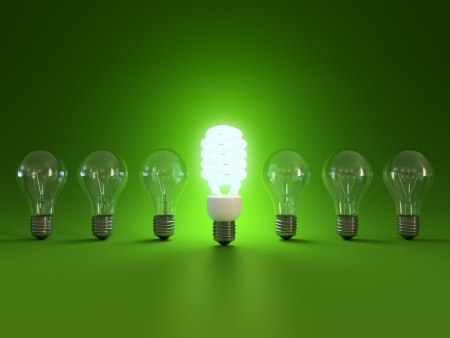savings: Energy saving and simple light bulbs isolated on green background. Stock Photo