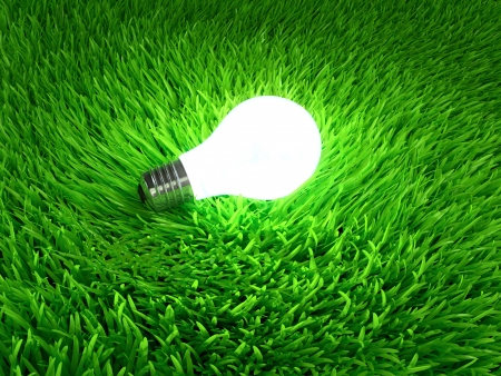 Glowing light bulb hanging above grass symbol of ecological energy photo