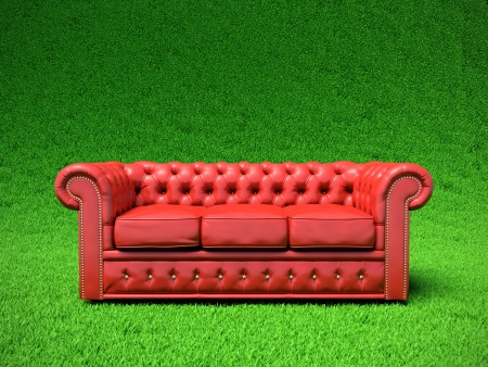 Red classic leather sofa on green field photo
