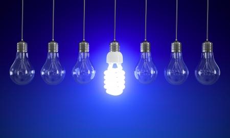 elektriciteit: Energiebesparing en eenvoudige gloeilampen geïsoleerd op een blauwe achtergrond.