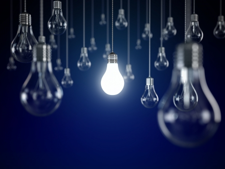 Hanging light bulbs with glowing one isolated on dark blue background Stock Photo