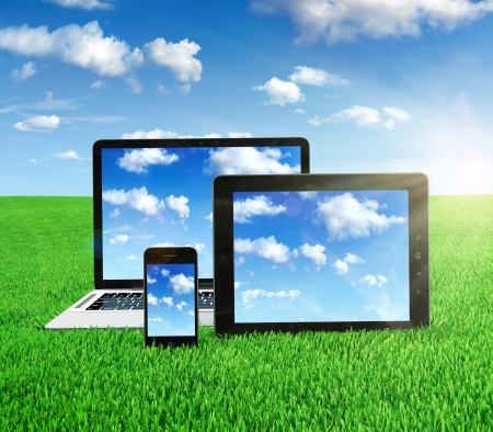 portable information device: Cloud computing concept on different electronic devices. Tablet computer, laptop and smartphone in the middle of the field with sky image on screen.