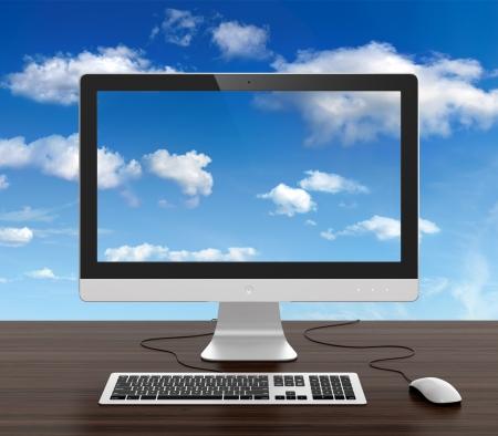 monitor de computadora: Monitor de la computadora con el teclado y el rat�n en el escritorio y el cielo nublado en el fondo.