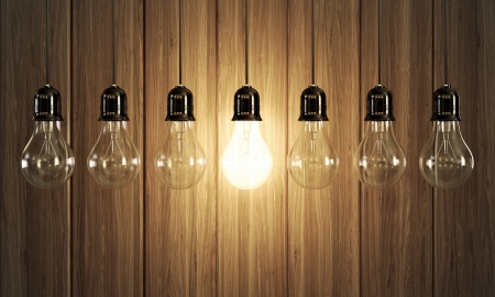 lit lamp: Seven light bulbs with glowing one on wooden background  Stock Photo