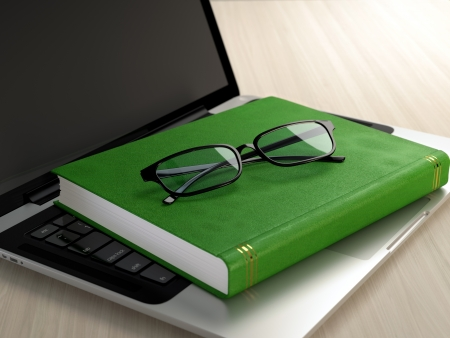 Laptop, green book and glasses on wooden desk  Electronic education concept