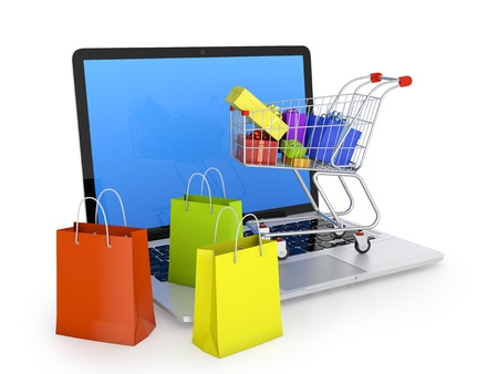 Laptop with shopping bags, shopping cart, and gift boxes isolated on white  Electronic commerce concept  photo