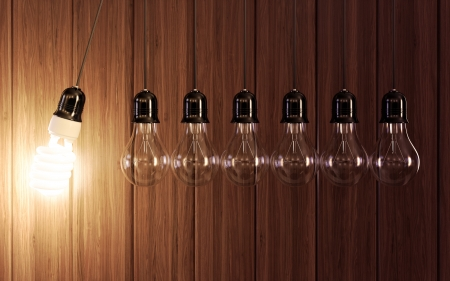 conserve: Light bulbs in perpetual motion with glowing energy saving one. Stock Photo