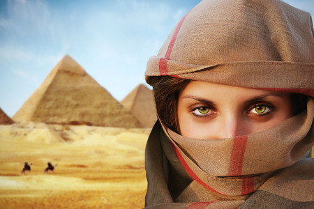 pyramid egypt: beautiful green eyed woman in chador and the pyramids