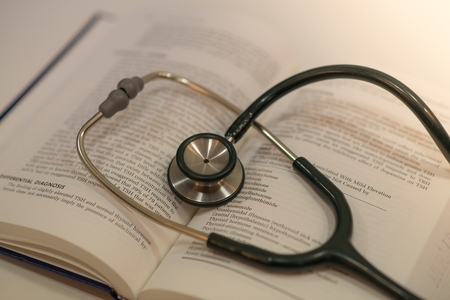 Medical concept with medical stethoscope and textbook selective focus