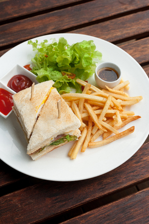 club sandwich with french fries on side on wood