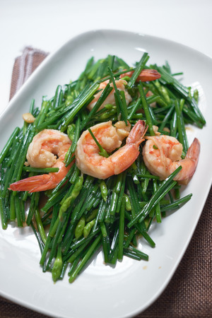 stir-fry flowering chinese chives with prawns and edamame in white plate Banco de Imagens